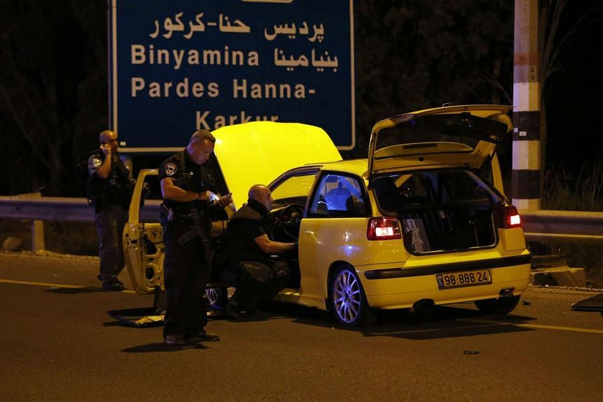 Israeli security forces and forensics inspect a car used by an Israeli Arab to attack a group of Jews near the northern Israeli kibbutz Gan Shmuel, on Sunday.