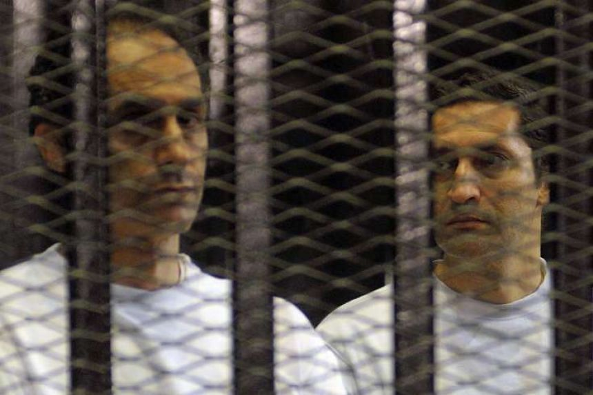 Alaa (right) and Gamal Mubarak, sons of ousted Egyptian president Hosni Mubarak, standing inside a cage in a courtroom during their verdict hearing in Cairo on Jun 2, 2012.