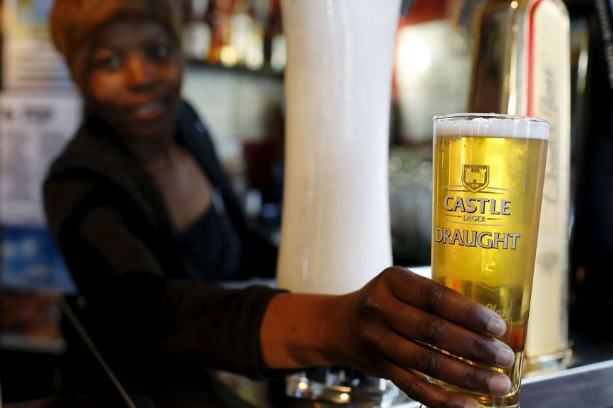 A file picture of a bartender serving beer produced by brewing company SAB Miller at a bar in Cape Town, September 16, 2015. Anheuser-Busch InBev has raised its offer for SABMiller takeover. PHOTO: REUTERS