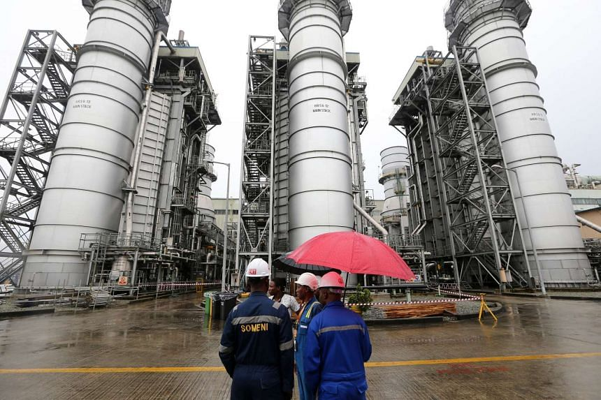 Workers stand beside power generating structures at the Afam VI energy generation plant, operated by the Shell Petroleum Development Company of Nigeria (SPDC).