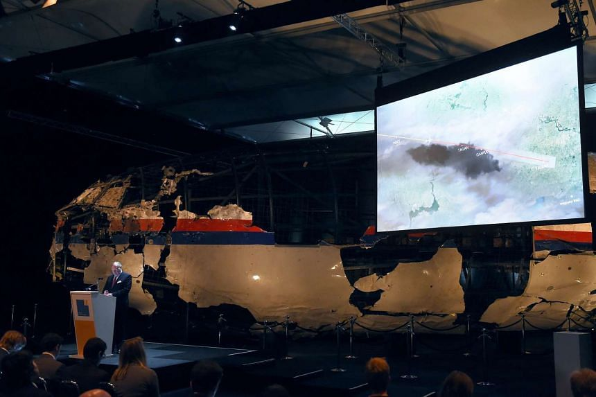 Dutch Safety Board Chairman Tjibbe Joustra speaks in front of the wrecked cockpit of Malaysia Airlines flight MH17 while a map is shown during a presentation at Gilze Rijen airbase on Oct 13, 2015.