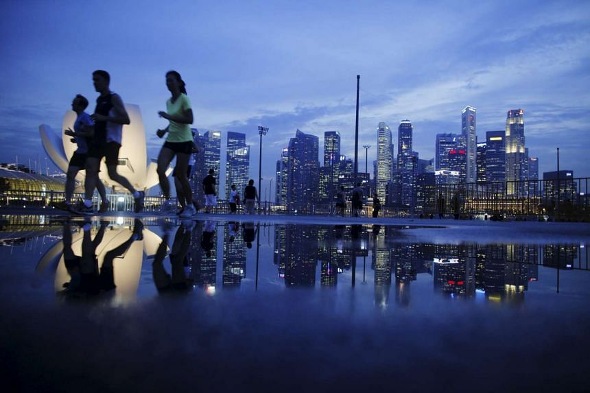Joggers run past the skyline of Singapore's financial district.