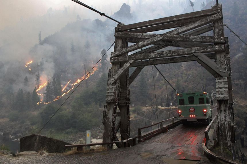 A wildfire is seen burning at the Manning Bridge near Riggins, Idaho, on Aug 29.