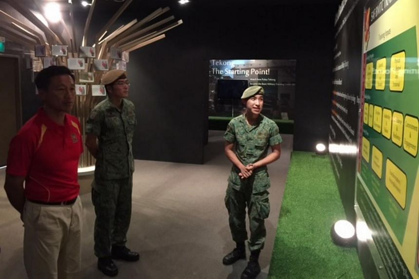 Senior Minister of State for Defence Ong Ye Kung viewing the BMT Journey exhibition.