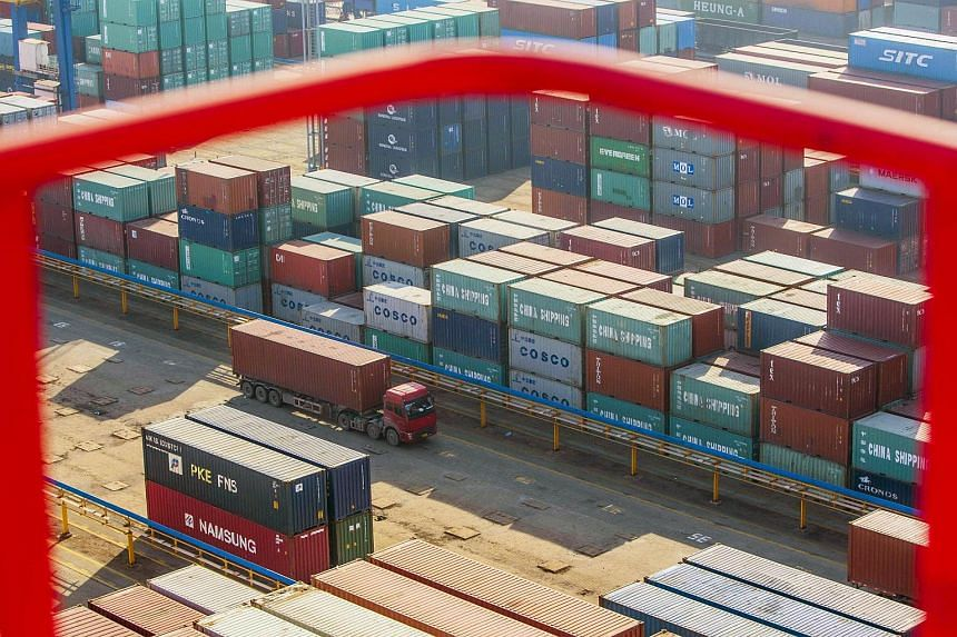 A truck drives past shipping containers at a port in Lianyungang, Jiangsu province, China.