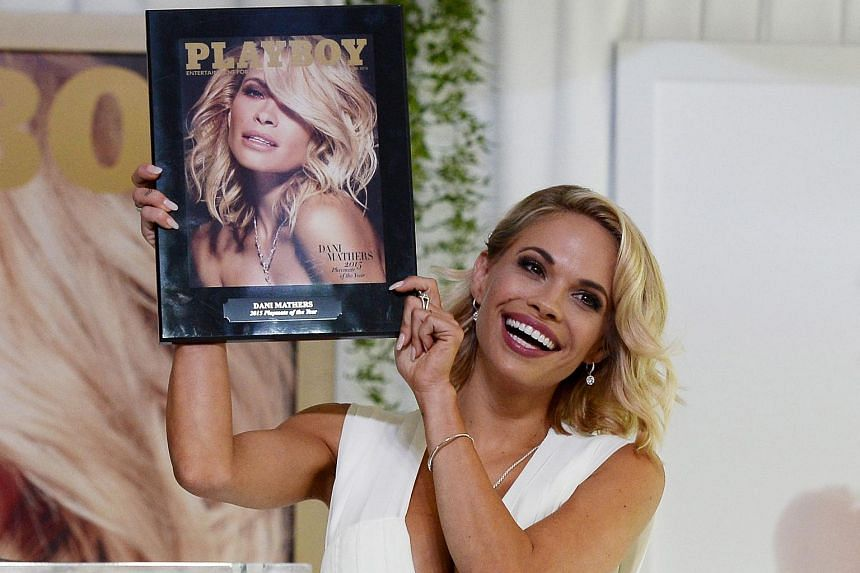 Playmate of the Year, Dani Mathers, holding a plaque with the cover of the Playboy June 2015 issue.