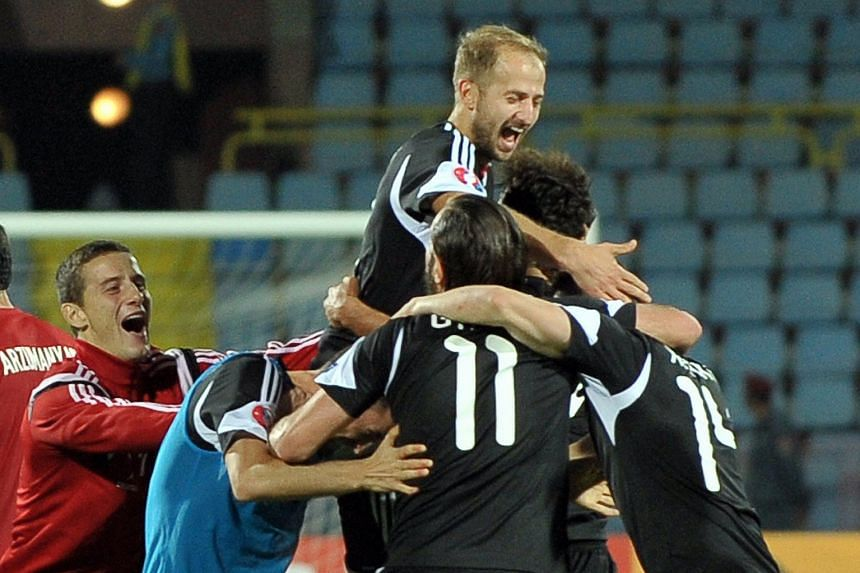 Albania's players celebrating their qualification for next year's European Championship after defeating Armenia 3-0 in Yerevan on Sunday. It is the first time the country, with a population of just 2.77 million, has reached a major football tournamen