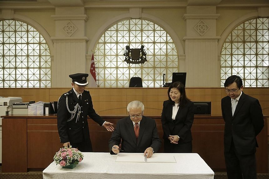 "President Tony Tan Keng Yam signing a guestbook after his tour of the State Courts and Family Justice Courts yesterday. It was his first visit to both courts. ""With the formation of these two institutions, our judicial system has become more effectiv"