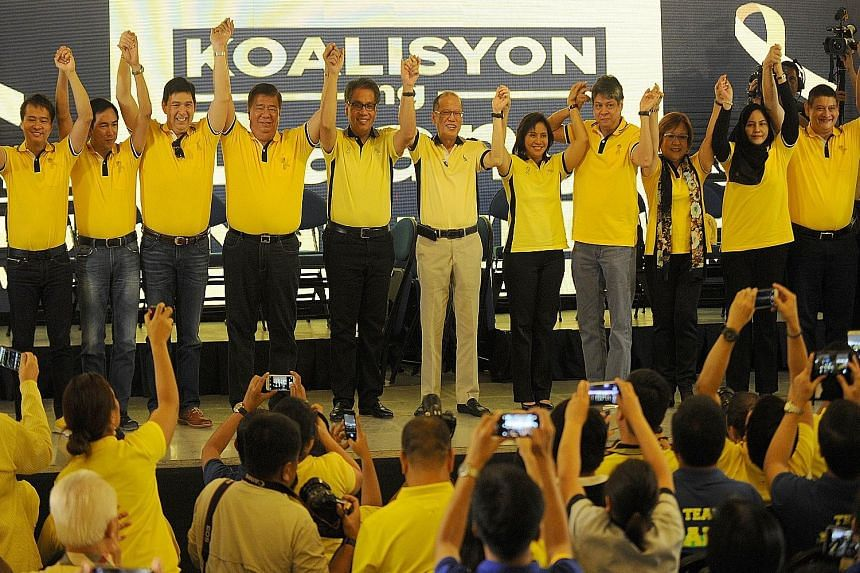 Philippine President Benigno Aquino (centre) holding hands with Mr Manuel Roxas and Ms Leni Robredo, his endorsed picks as candidates for president and vice-president, respectively, for the May 9 election next year. Mr Aquino yesterday also introduce
