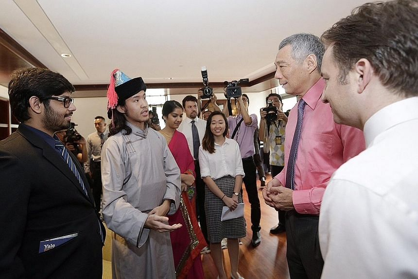 Prime Minister Lee Hsien Loong speaking with students, some in their ethnic costumes, at the inauguration of the college campus yesterday, as Yale-NUS founding president Pericles Lewis (far right) looked on. Mr Lee says the college needs a curriculum