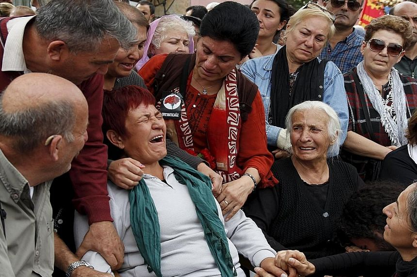 Family members of a victim of last Saturday's bomb blasts mourning over his coffin during a funeral ceremony in Ankara, Turkey, on Sunday. Ninety-seven people were killed in the attack targeting a major peace rally. It never took place.