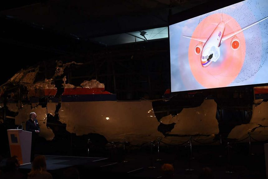 Dutch Safety Board Chairman Tjibbe Joustra speaks in front of the wrecked cockpit of Malaysia Airlines flight MH17 as a simulation plays onscreen showing where the missile struck the aircraft, at Gilze Rijen airbase on Oct 13, 2015.