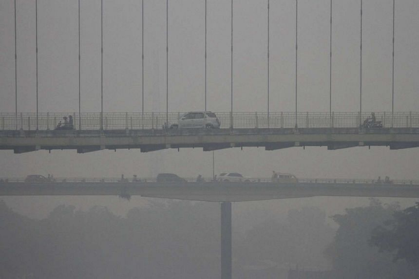 Vehicles driving along Siak Bridge, shrouded by haze, in Pekanbaru, Indonesia's Riau province on Oct 11, 2015, in this picture taken by Antara Foto.