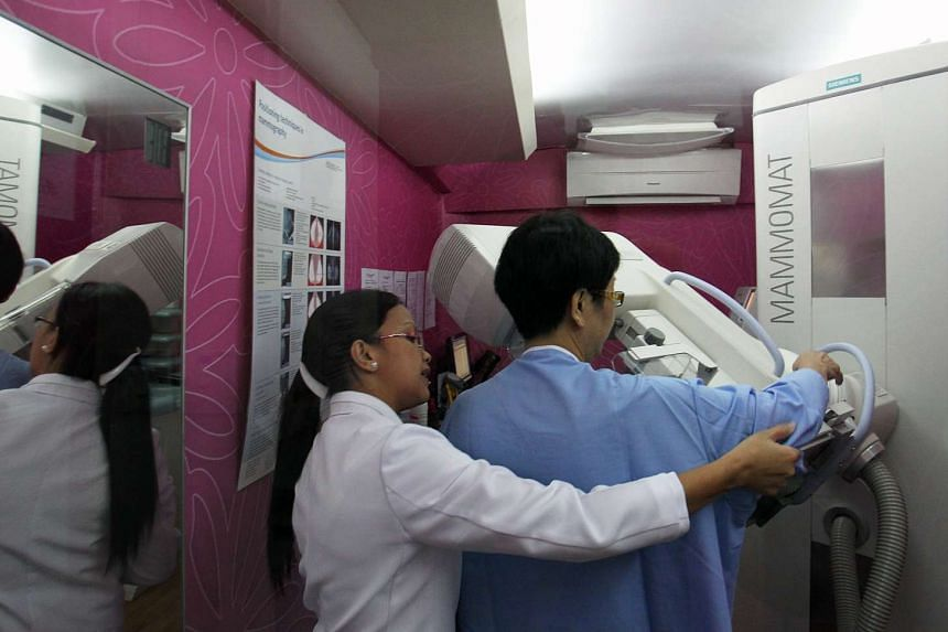 A radiographer and mammographer prepares a woman for a mammogram.