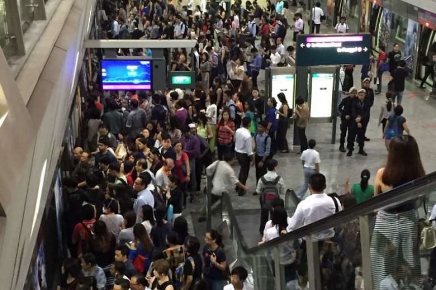 Commuters at Hougang NEL train station platform.