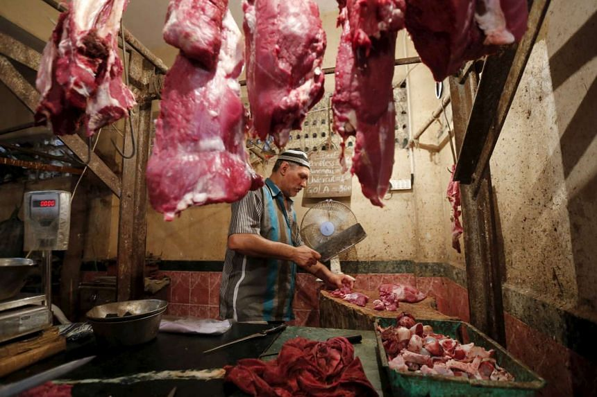A butcher cutting meat for a customer inside his shop in Mumbai, India, on Sept 8, 2015.
