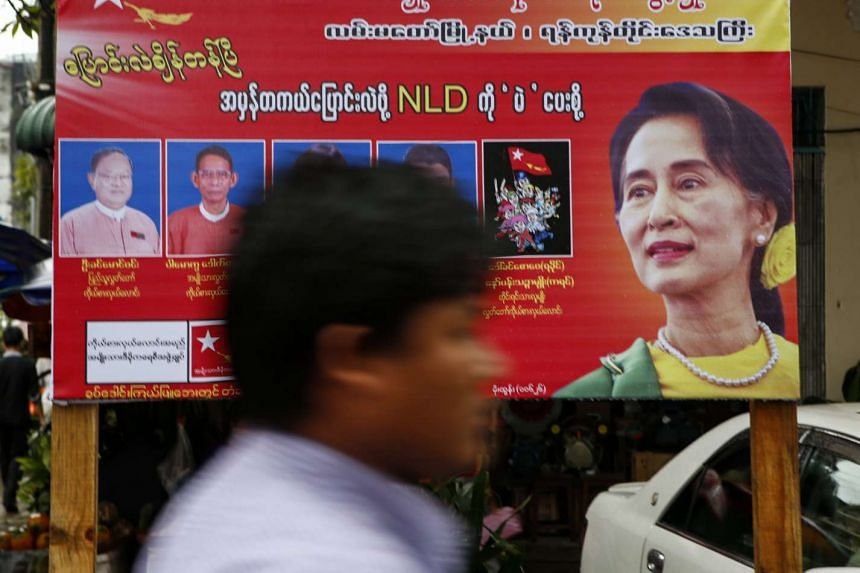 A man walks in front of a National League for Democracy (NLD) campaign poster with images of Myanmar opposition leader Aung San Suu Kyi and her party's candidates, at a downtown area in Yangon, Myanmar, on Oct 13, 2015.