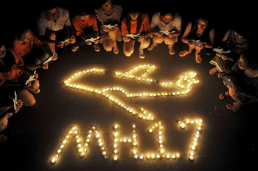 College students gather around candles forming the shape of an airplane, during a candlelight vigil for victims of the downed Malaysia Airlines Flight MH17, at a university in Yangzhou, Jiangsu province, on July 19, 2014.