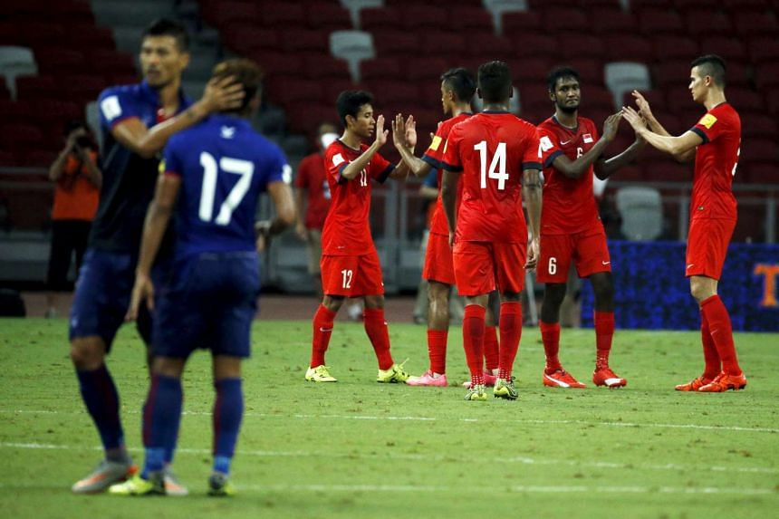 Singapore's players celebrate defeating Cambodia (blue) at the end of their 2018 World Cup qualifying match at the National Stadium in Singapore Oct 13, 2015.