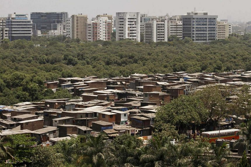 High-rise buildings stand behind slum dwellings in Mumbai on May 9, 2012.