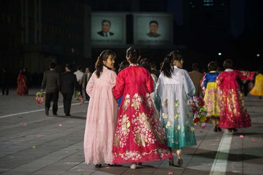 North Korean women wearing traditional hanbok dresses walk on Kim Il-Sung square following a mass military parade in Pyongyang on Oct 10, 2015.