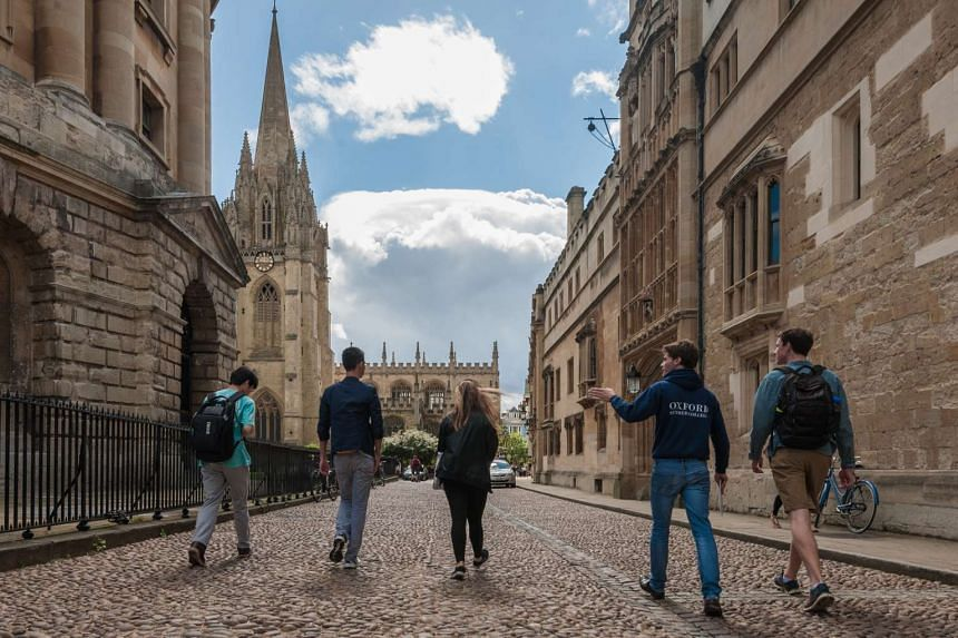 Students walking near the Radcliffe Camera, a famous library building at Oxford University.