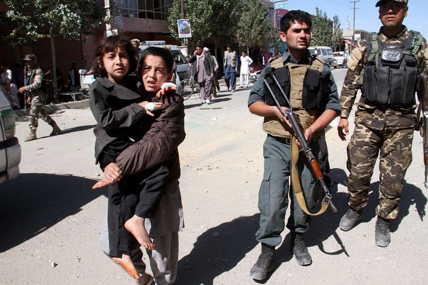 A boy helps his injured sister at the scene of a bomb blast that targeted a Police vehicle in Ghazni, Afghanistan on Oct 4.