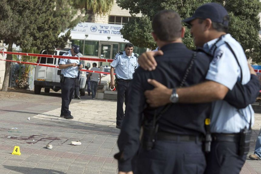 Israel police embrace at the scene of a Palestinian woman who knifed an Israeli policeman and then was shot nearby the main Jerusalem police station located in Arab East Jerusalem near French Hill on Monday.