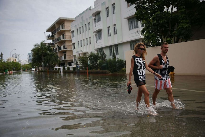 People walk through a flooded street in Miami Beach, Florida on Sept 29 this year that was caused in part by what many believe is the rising sea levels due to climate change.