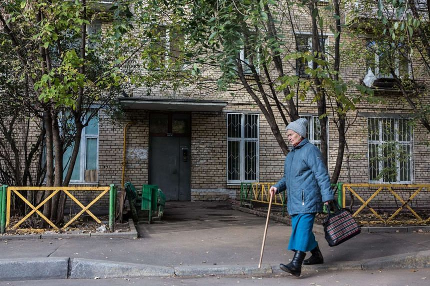 An old woman passes an apartment house on Monday where Russian security services detained a group of peeople on suspicion of preparing a terror attack in Moscow.