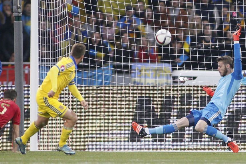 Spain's goalkeeper David de Gea (right) makes a save on Ukraine's Ruslan Rotan during the Euro 2016 group C qualifying soccer match at the Olympic stadium in Kiev, Ukraine on Monday.