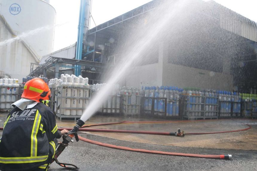 A firefighter from the Singapore Civil Defence Force at work outside Leeden National Oxygen yesterday. A woman employee died in the fire at the gas manufacturing firm in Jurong. Its emergency response team helped to control the blaze before firefight