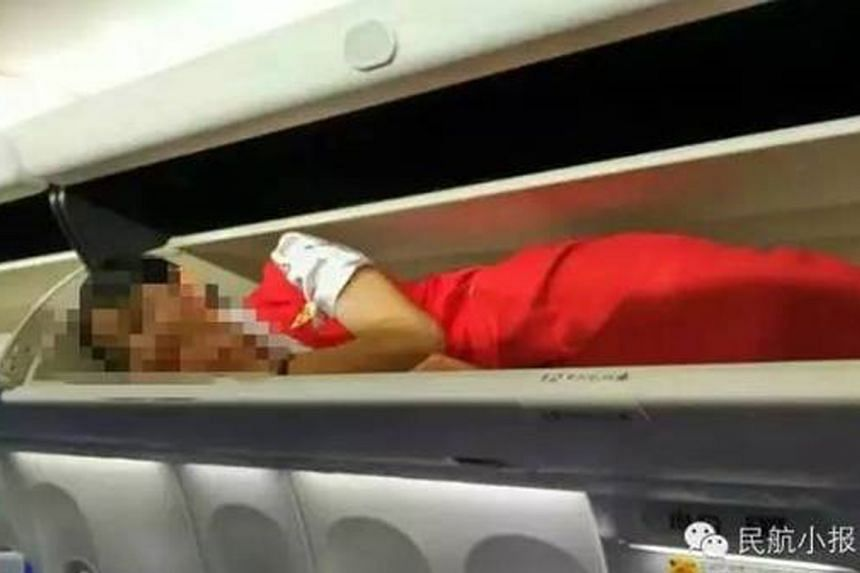 """A social media user in China has posted pictures of new Kunming Airlines' cabin crew being forced into overhead compartments as a """"rite of passage"""". The post went viral, and the airline has pledged an investigation, saying it had no knowledge o"""