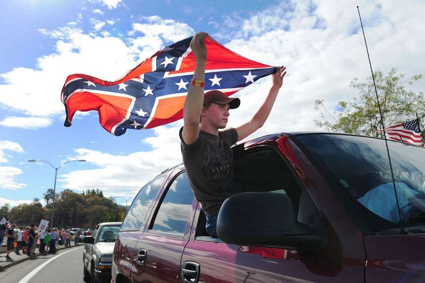 Chance White holding a confederate flag as he drives past protesters lining the street in front of the Roseburg Regional Airport on Oct 9, 2015, in Roseburg, Oregon.