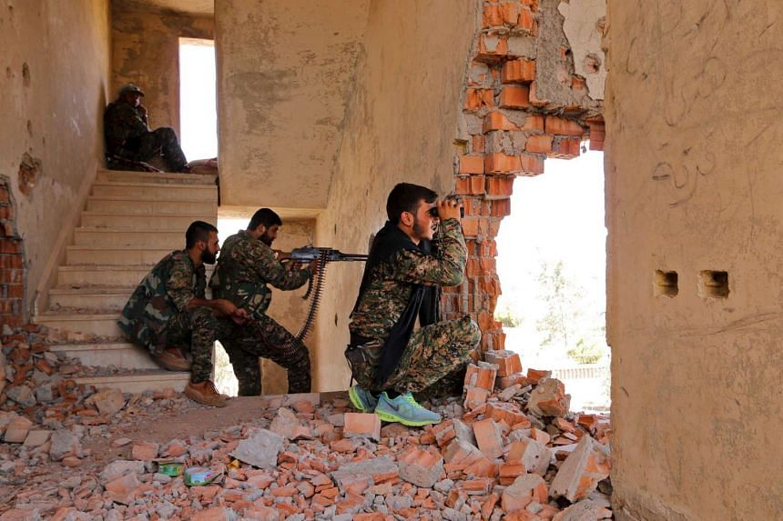 Kurdish People's Protection Units (YPG) fighters take up positions inside a damaged building as they monitor ISIS positions, in the al-Vilat al-Homor neighbourhood in Hasaka, Syria, on July 22, 2015.