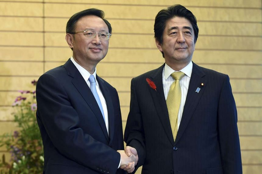 Chinese State Councilor Yang Jiechi (left) shakes hands with Japanese Prime Minister Shinzo Abe prior to their meeting at the prime minister's official residence in Tokyo, Japan, on Oct 14, 2015.