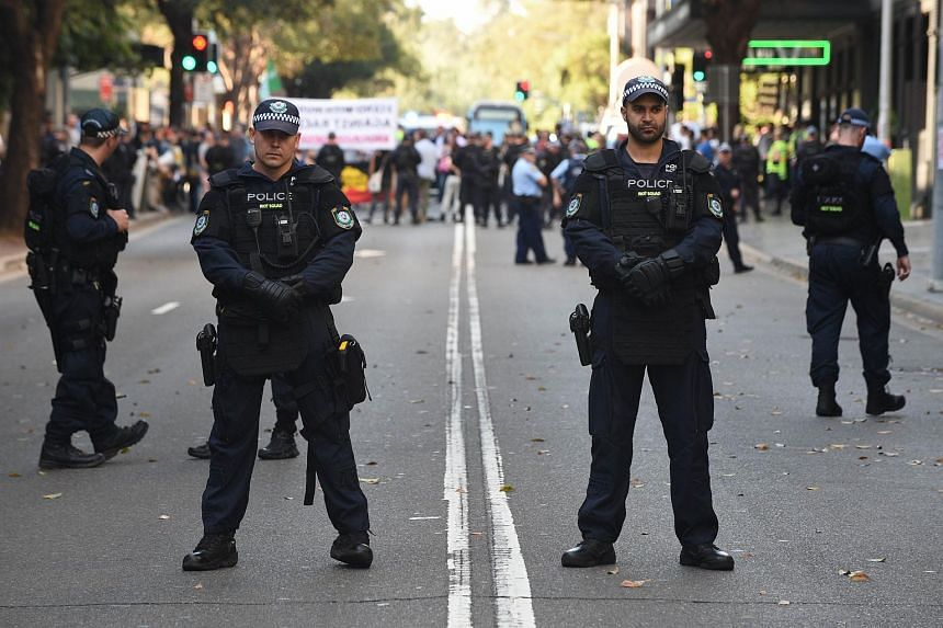 Riot police stand guard as anti-Muslim protesters hold a demonstration outside the Parramatta Mosque in Sydney on Oct 9, 2015.