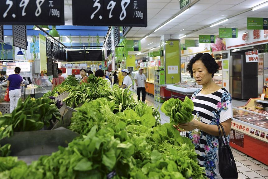 A customer selecting vegetables at a supermarket in Hangzhou on Sept 10.
