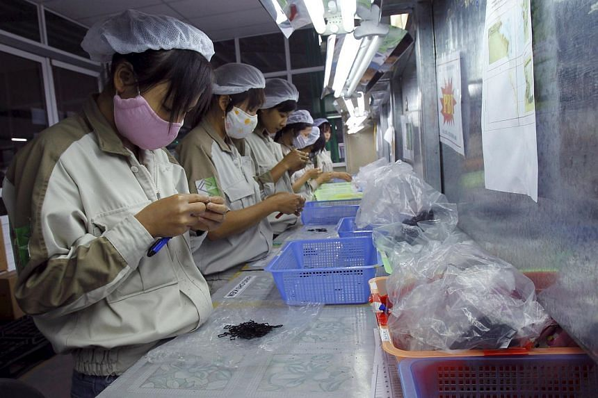Women working at a plastic factory, which makes plastic parts for electronic production, in Que Vo district, outside Hanoi.