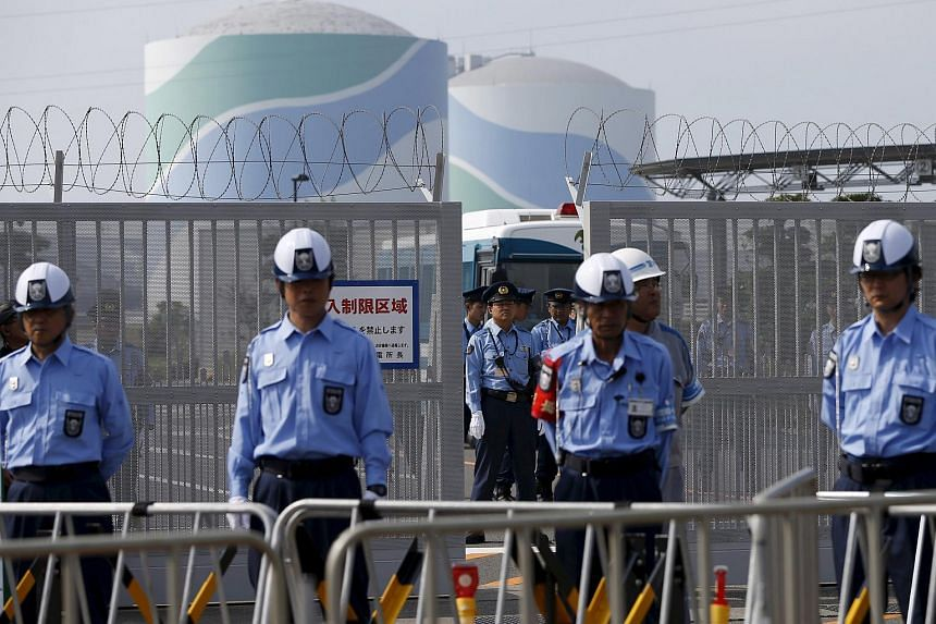 Police officers and security personnel stand guard at an entrance of Kyushu Electric Power's Sendai nuclear power station, during a protest demanding for the stop of the plant's restart on Aug 9, 2015.