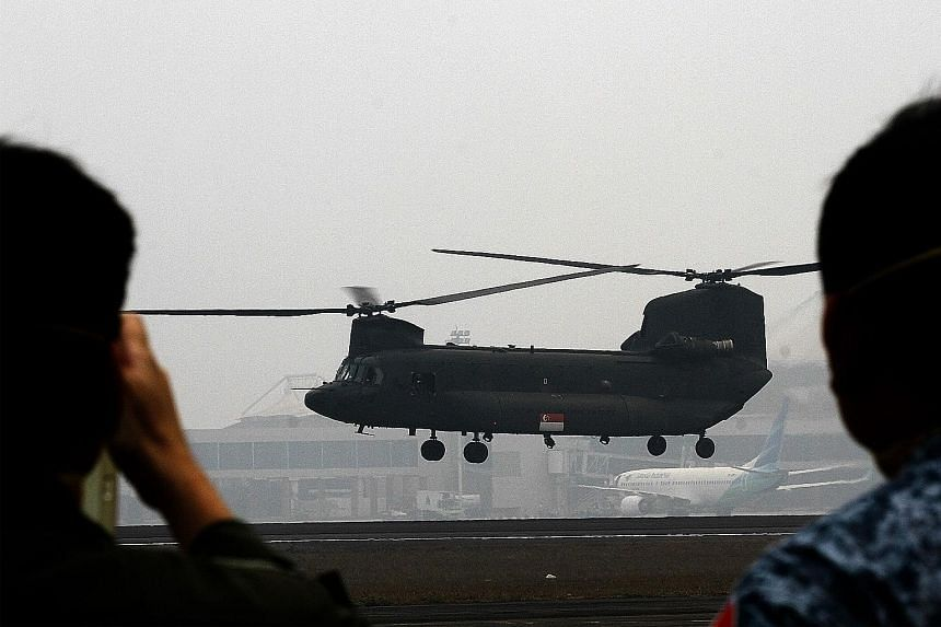 A Republic of Singapore Air Force Chinook helicopter, carrying a crew of Singapore military and civil defence personnel, takes off from the haze-covered Indonesian airbase in Palembang, Sumatra, on Monday, for its first aerial water-bombing mission o