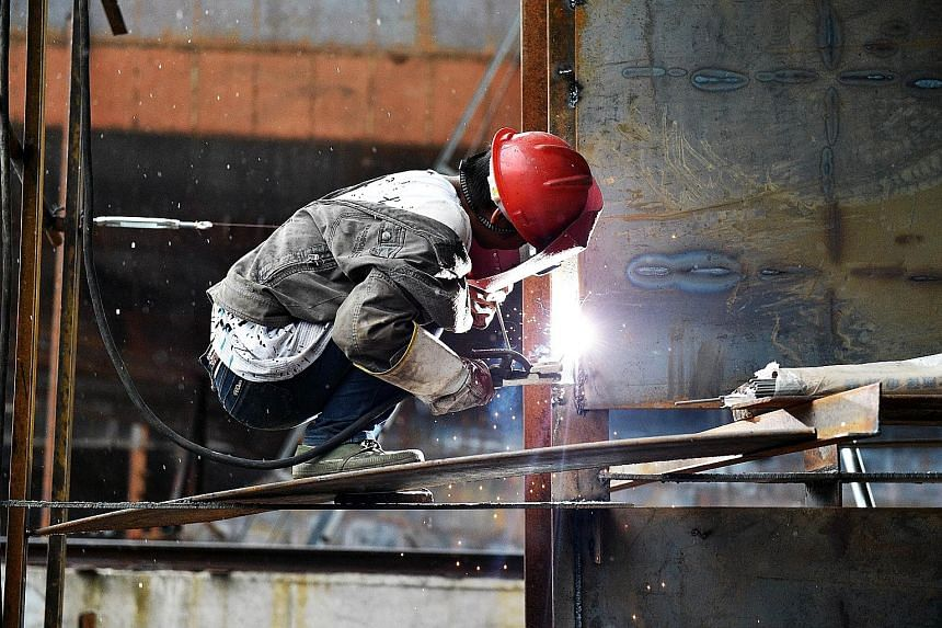 A worker welding a part of a cargo ship in a shipyard in China's south-west Chongqing municipality. Chinese imports slumped by 20.4 per cent in September from a year earlier, posting an 11th straight decline.