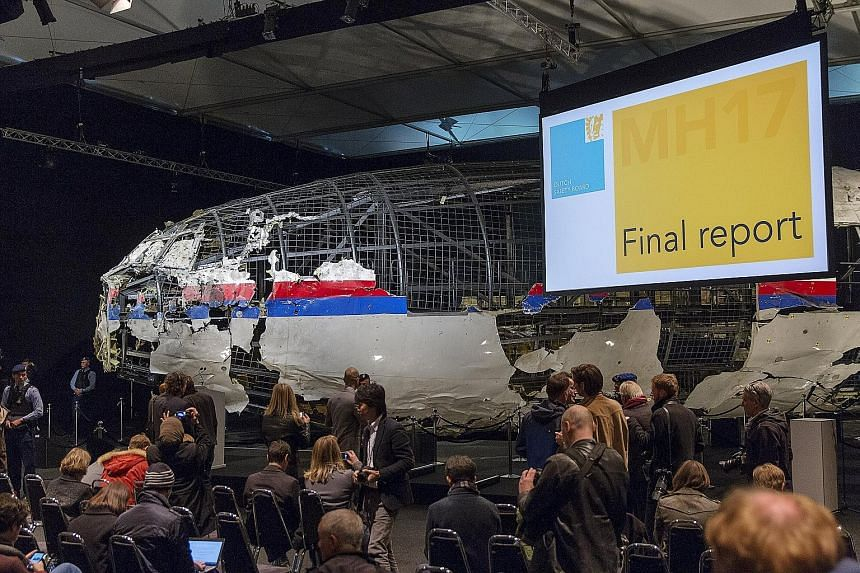 The reconstructed aeroplane serving as a backdrop during the presentation of the final report into the crash of Malaysia Airlines Flight MH17 in Gilze-Rijen, the Netherlands, yesterday. The report by an international team of investigators led by the