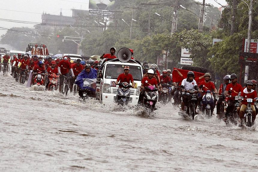 People riding motorbikes and bicycles on a flooded street during a National League for Democracy (NLD) election rally in Mandalay, Myanmar, yesterday. Myanmar's elections will take place as scheduled on Nov 8, state television reported yesterday afte