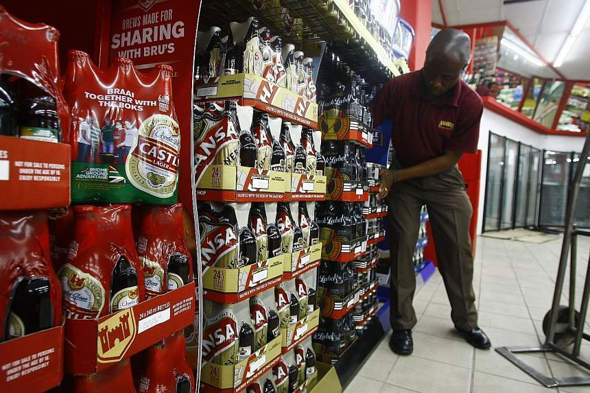 An employee restocking SABMiller beer products at a Durban City Bottle store in Durban, South Africa. Anheuser-Busch InBev will pay £44 a share in cash for a majority of the shares in its nearest competitor.