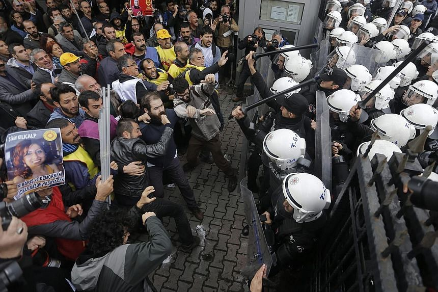 Protesters clashing with Turkish riot police during an anti-government demonstration in Istanbul yesterday. Turkish investigators were seeking to firm up suspicions that members of the Islamic State in Iraq and Syria were behind the double suicide bo