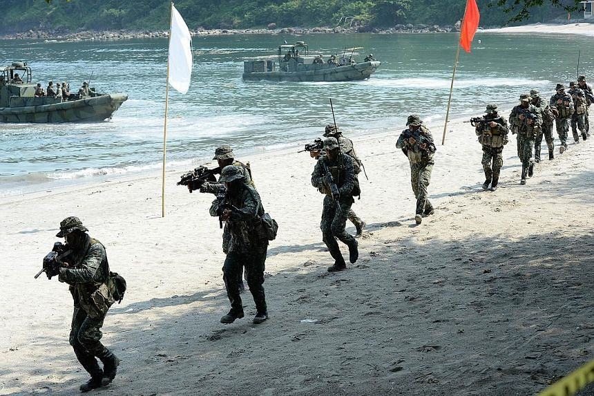 "Philippine Marines simulating a beach landing as part of their annual joint naval exercises with the US in Cavite province, west of Manila, last week. The US says it is planning ""freedom of navigation"" patrols near artificial islands built by China i"