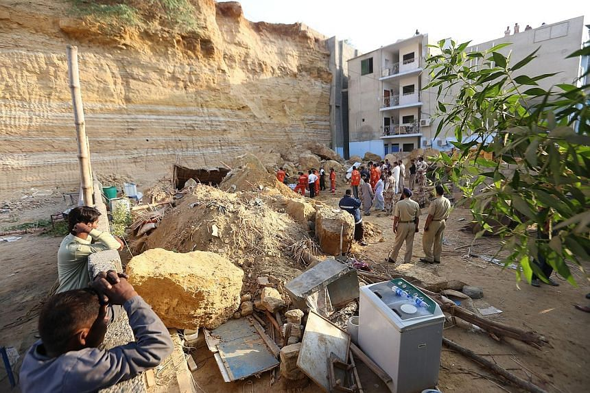 People surveying the debris of a landslide in Karachi, Pakistan, yesterday. At least 13 people were buried alive when their shacks were hit by the landslide, police and rescue workers said, with one victim believed to be as young as six months. Senio