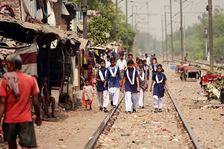 People at the railway tracks near a slum area of New Delhi yesterday. The four-year-old girl who was raped was found unconscious with her face and body slashed on the tracks last Friday.