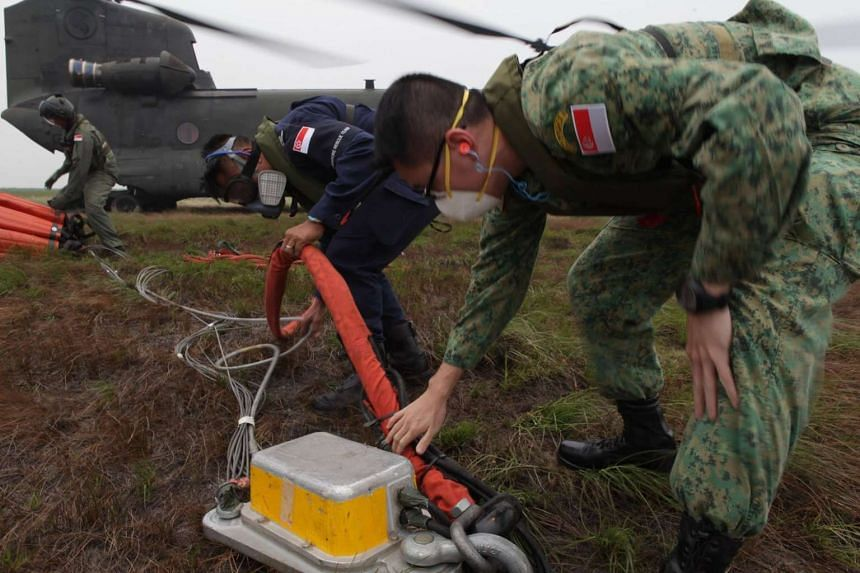 SAF and SCDF officers working to prepare a Chinook helicopter for firefighting duties in Palembang.
